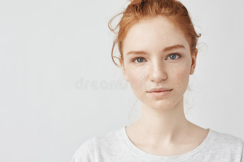 Close up portrait of young beautiful redhead girl in white shirt smiling looking at camera. Copy space. Isolated on. Close up portrait of young beautiful redhead royalty free stock photo