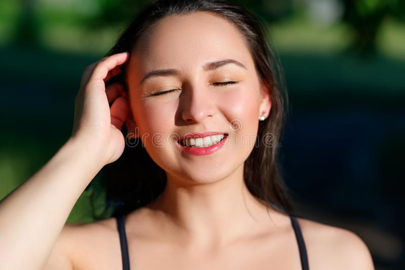 Close up portrait of a young beautiful smiling happy brunette girl in outdoor Park on a Sunny summer day correcting hand loose royalty free stock photo