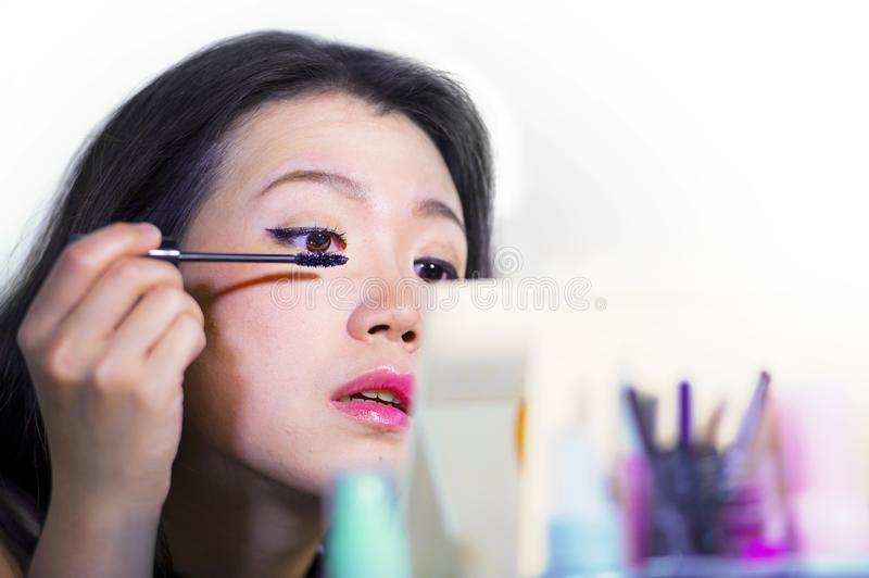 close up portrait of young beautiful and sweet Asian Chinese woman 20s or 30s applying mascara on her eye in make up session look royalty free stock image