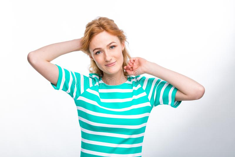 Close-up portrait of a young, beautiful woman with red curly hair in a summer dress with strips of blue in the studio on a gray ba stock photos