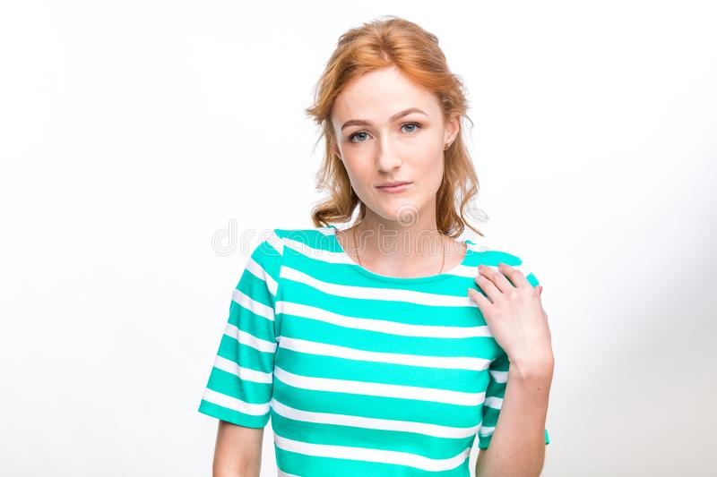 Close-up portrait of a young, beautiful woman with red curly hair in a summer dress with strips of blue in the studio on a gray ba stock images
