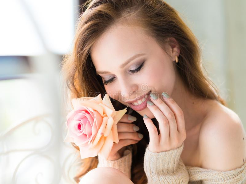 Close-up portrait of young beautiful woman smile mouth with pink rose flower and touch her face. Skin care and woman`s royalty free stock photos