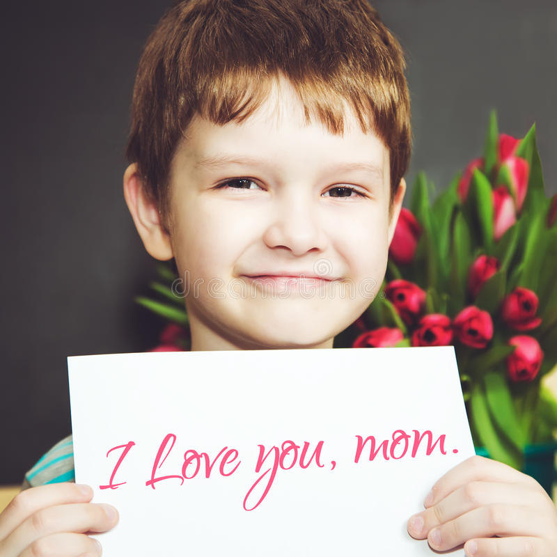Close-up portrait young boy holding a piece of paper with the words 'I love you mom.' stock photography