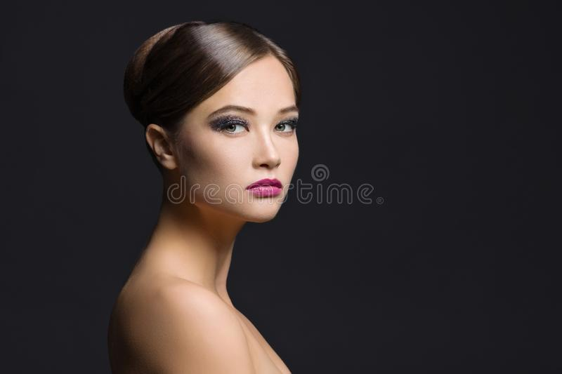 Close-up portrait of young brunette girl with brushed hair, evening make-up, naked shoulders and long neck. Woman looking at camer royalty free stock images
