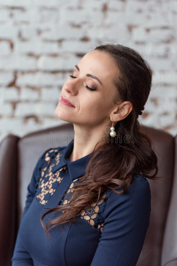 Close up portrait of a young brunette woman in a blue dress sitting on a chair with eyes closed dreamily royalty free stock image