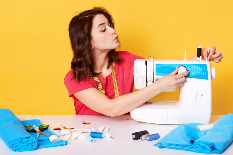 Close up portrait of young brunette woman who works as seamstress, wears red casual t shirt, sews baby clothes on sewing machine, stock images
