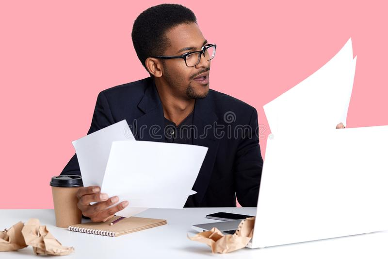Close up portrait of young businessman, has dark skin, wears black jacket, sitting at white desk, reading document with astonished royalty free stock images
