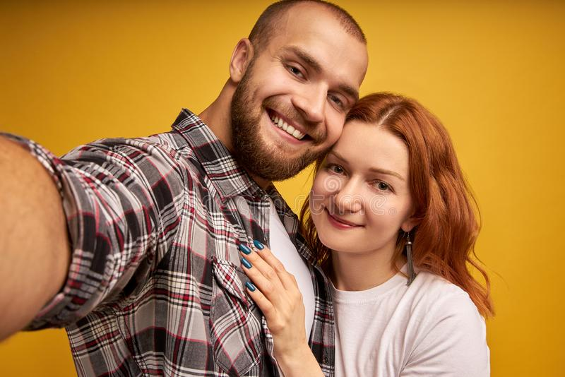 Close up portrait of young, caucasian, attractive, lovely, positive couple in shirts making selfie on mobile phone over yellow royalty free stock photos