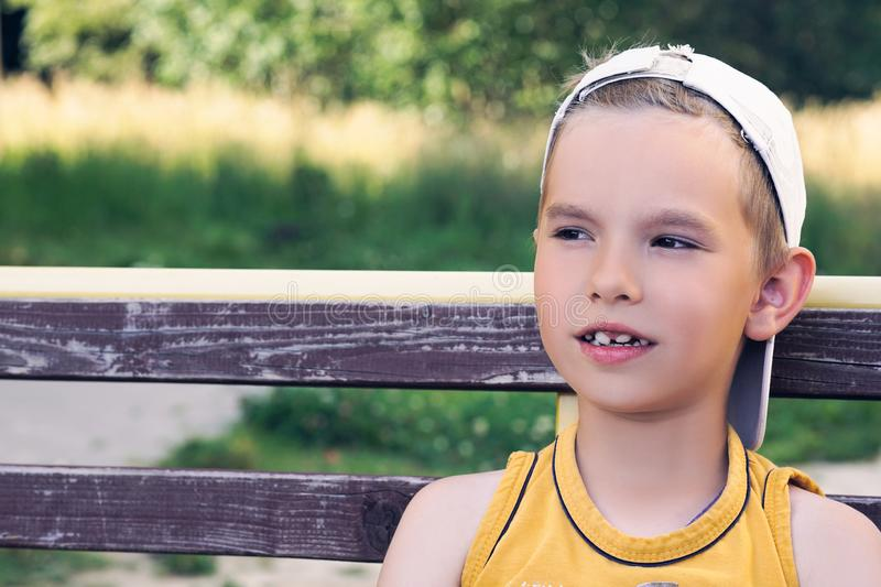 Close up portrait of young caucasian boy sitting on bench at the park. stock images