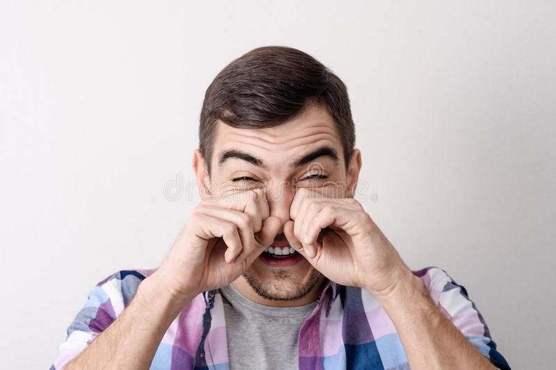 Close-up portrait of a young Caucasian man, rubs his eyes with his hands from tears of laughter, grief, pain stock photo