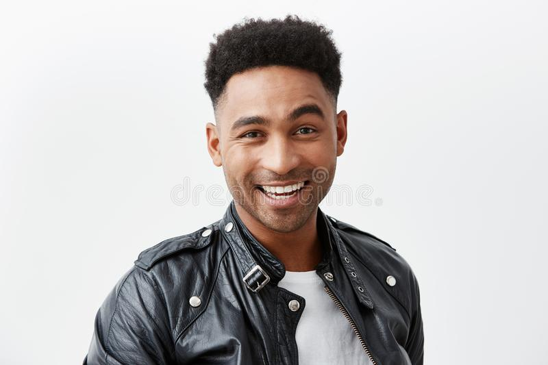 Close up portrait of young cheerful dark-skinned american man with curly hair in white t-shirt and leather jacket royalty free stock photos