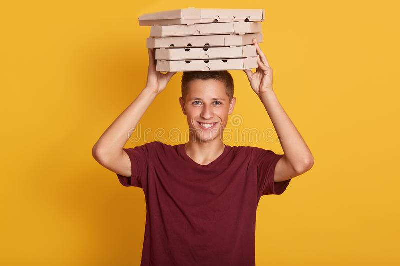 Close up portrait of young cheerful delivery man with red t-shirt standing,holding stack of cardboard pizza boxes on grey royalty free stock photography