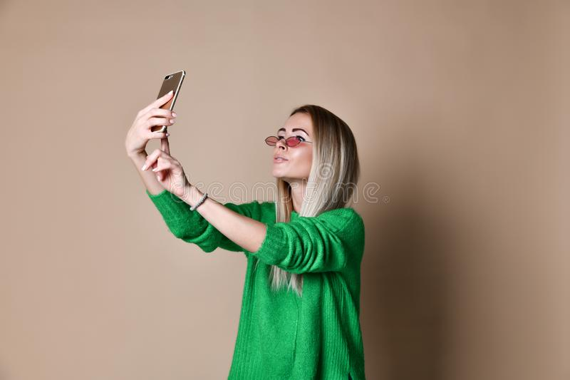 Close-up portrait of young cheerful fashion blonde woman in sweater wear makes selfie on smartphone, over beige background stock image