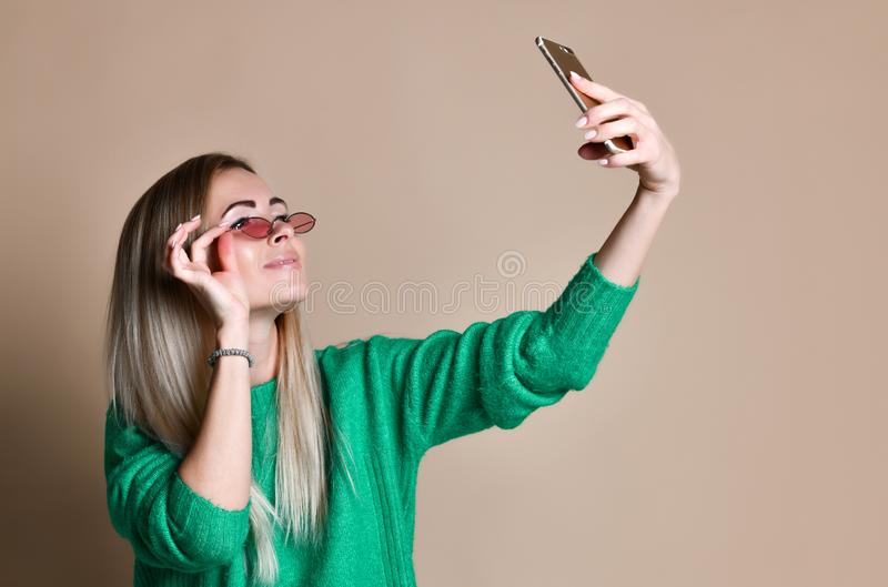 Close-up portrait of young cheerful fashion blonde woman in sweater wear makes selfie on smartphone, over beige background stock photo