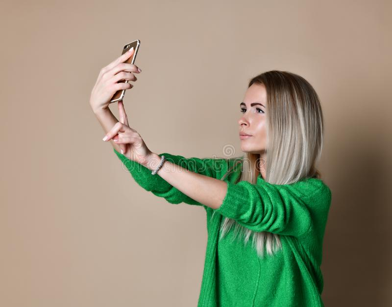 Close-up portrait of young cheerful fashion blonde woman in sweater wear makes selfie on smartphone, over beige background. stock photo
