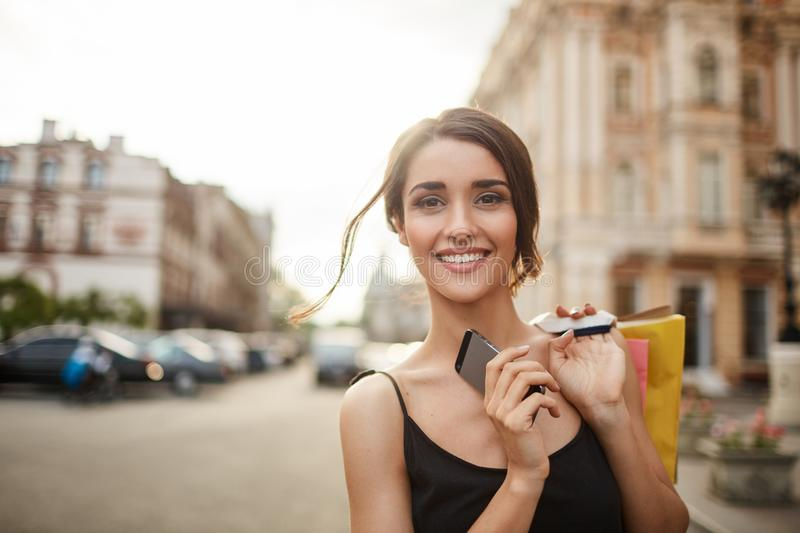 Close up portrait of young cheerful handsome girl with dark hair in black clothes looking in camera with relaxed smile. Holding cellphone and shopping bags in stock photos