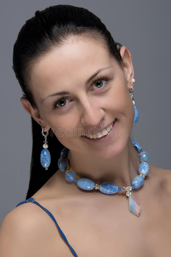 Portrait of cheerful girl with earrings and necklace. Close up portrait of young cheerful woman wearing vivid earrings and necklace of light blue stones. Natural royalty free stock photo
