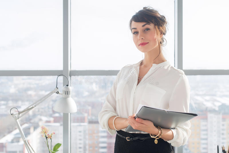 Close-up portrait of a young confident female office manager at her workplace, ready for doing business task. stock photo