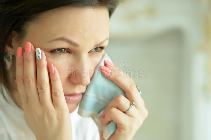 Close up portrait of young crying woman posing at home royalty free stock images