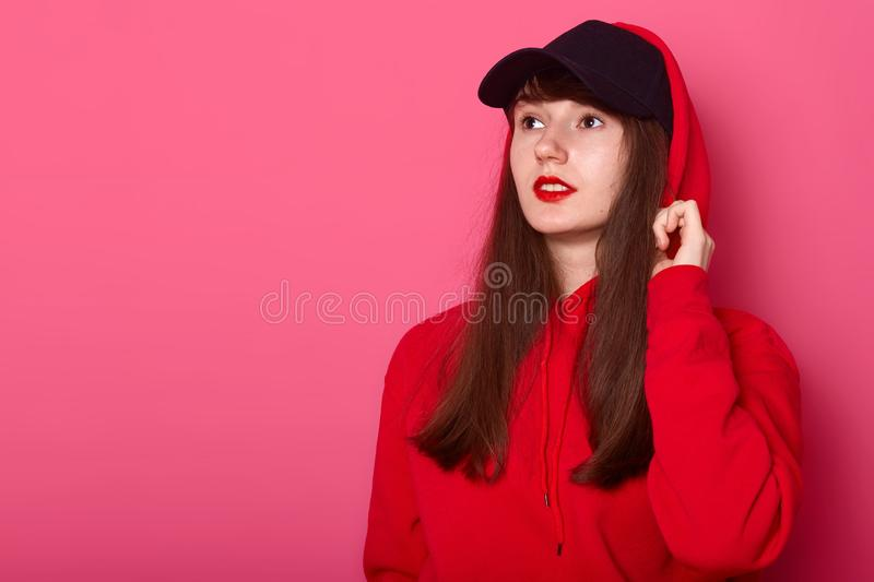Close up portrait of young cute brunette teenager girl in casual red hoodie and cap, posing with bright listick on pink background. Looking aside at copy space royalty free stock photography