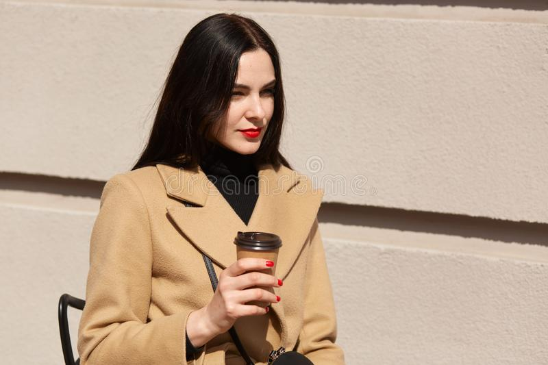Close up portrait of young dark haired elegent woman sitting at street cafe, drinking coffee from paper cup, looks pensively away royalty free stock photos