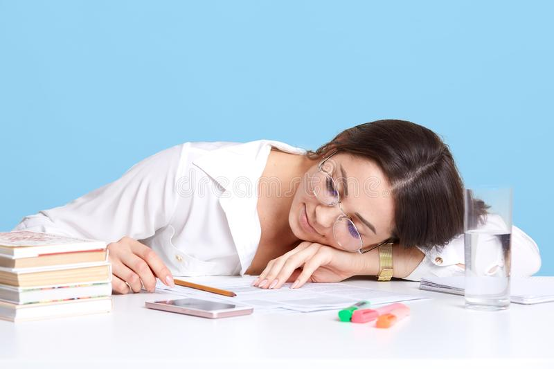Close up portrait of young dark haired woman sitting at white desk, student sleeping and lying on her books, female tired of long royalty free stock image