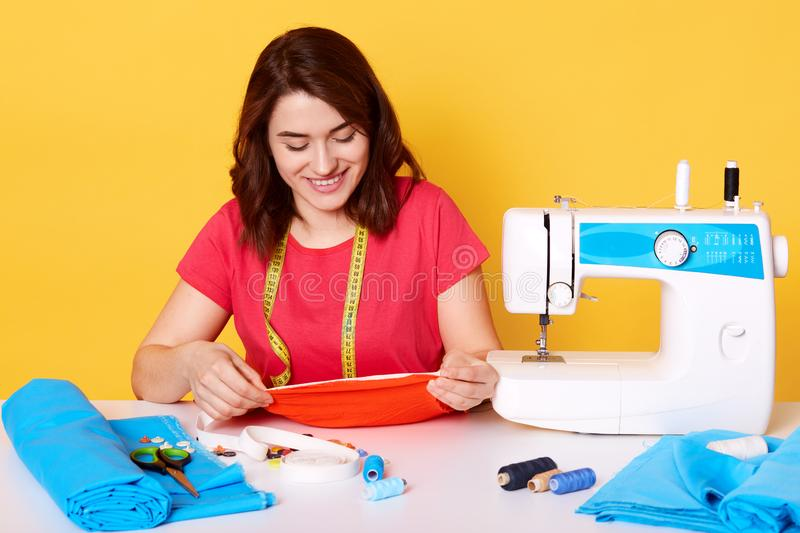 Close up portrait of young dressmaker woman sews clothes on sewing machine, looks smiling down on her creation, holds pieceof red stock photo