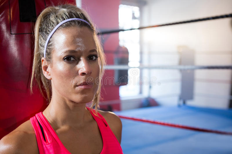 Close-up portrait of young female athlete against boxing ring stock images
