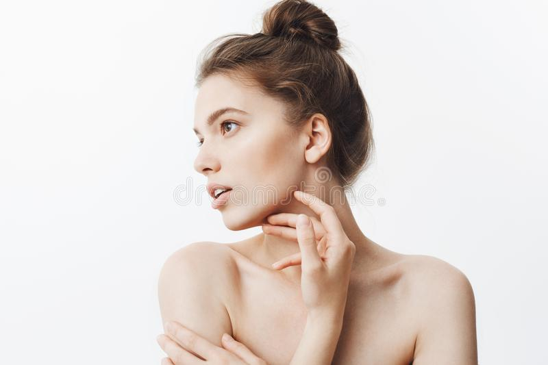 Close up portrait of young female brunette student girl with bun hairstyle and baked shoulders looking aside with calm royalty free stock photography