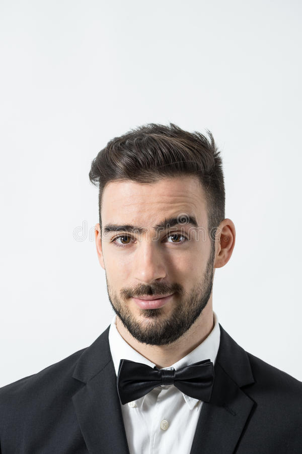 Close up portrait of young friendly charming gentleman with raised eyebrow looking at camera royalty free stock photo