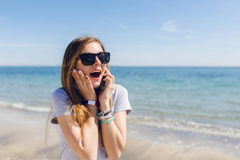 Close-up portrait of young girl with long hair standing near blue sea. She wears black sunglasses. She is surprised at royalty free stock image