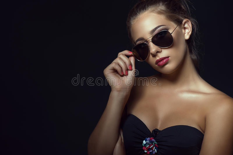 Close up portrait of young gorgeous tanned model wearing trendy aviator sunglasses stock images