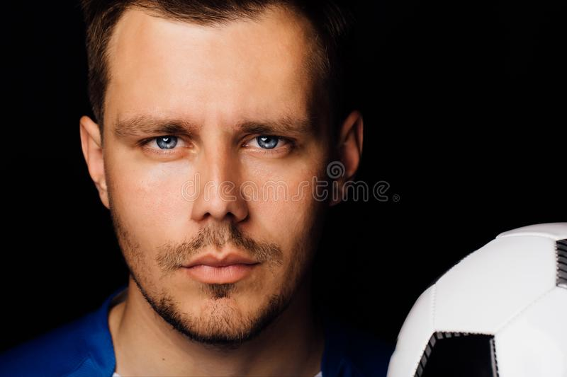 Close-up portrait of young handsome football player soccer posing on dark background. royalty free stock image