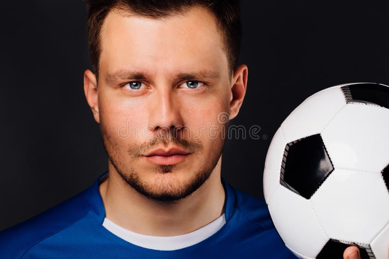 Close-up portrait of young handsome football player soccer posing on dark background. royalty free stock photos