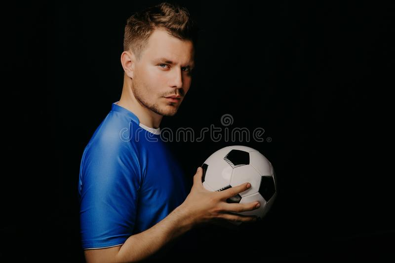 Close-up portrait of young handsome football player soccer posing on dark background. stock photos