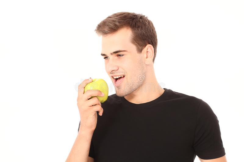 Close up portrait of a young handsome man eating apple isolated on white in black shirt. Copy space. Healthy lifestyle stock photography