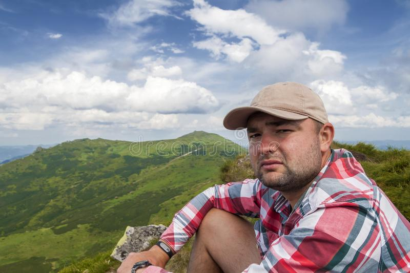 Close-up portrait of young handsome tourist man in summer clothing looking in camera on green grassy mountains and bright blue sky stock photography