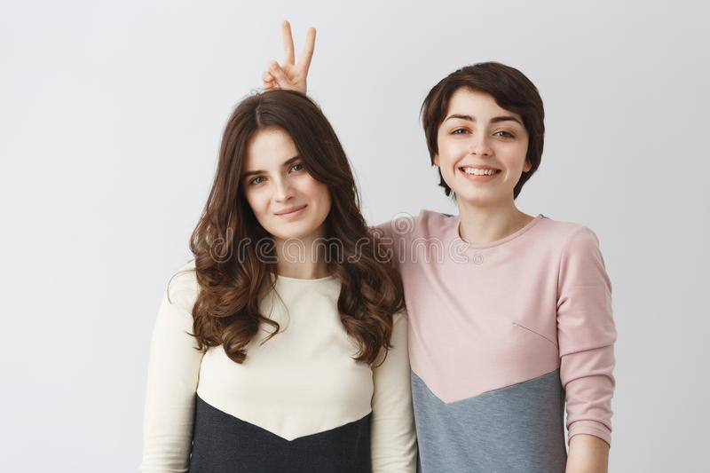 Close up portrait of young happy lesbian pair with dark hair in matching clothes smiling, having fun, posing for shoot stock image