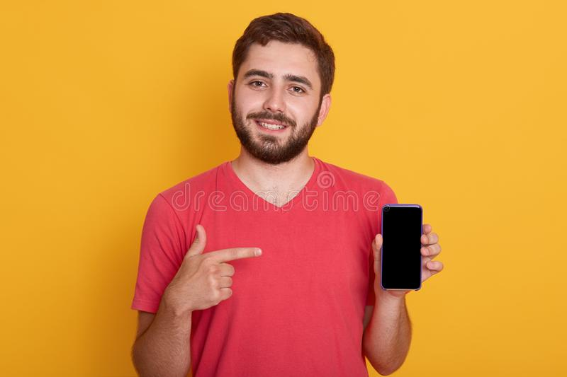 Close up portrait of young happy man in red shirt showing black blank smart phone screen, looking at camera, poses over yellow royalty free stock photos