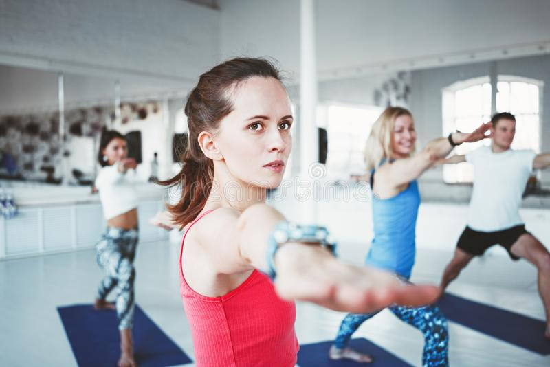 Close up portrait of young healthy woman doing yoga exercise indoor class together with group. Blurred background royalty free stock photos