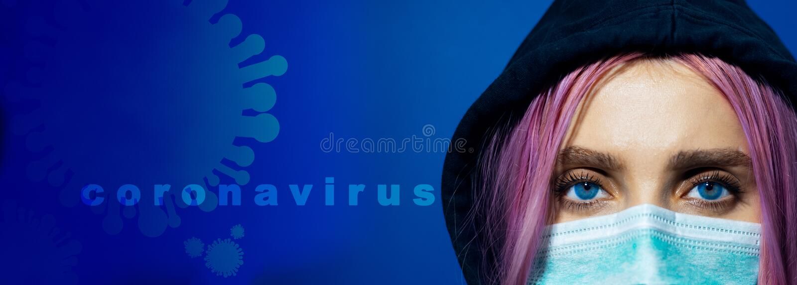 Close-up portrait of young hooded girl with blue eyes and pink hair, wearing medical flu mask with text and icon of coronavirus. Close-up portrait of young stock photos