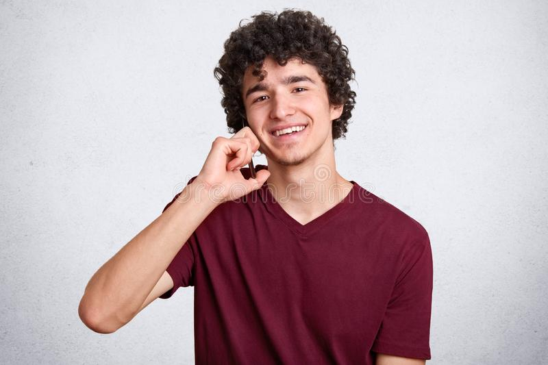 Close up portrait of young man with curly hair, in maroon t shirt talking on phone while looking at camera isolated over white stock image