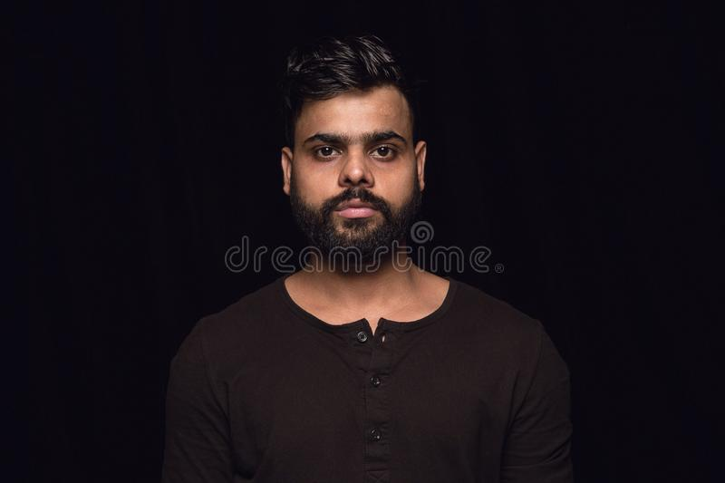 Close up portrait of young man isolated on black studio background. Close up portrait of young hindoo man isolated on black studio background. Photoshot of real stock photos