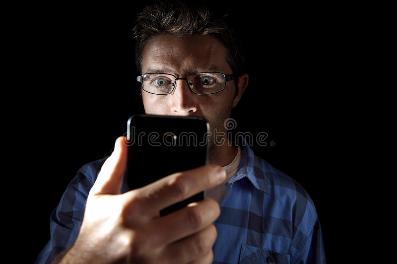 Close up portrait of young man looking intensively to mobile phone screen with blue eyes wide open isolated on black background stock photo