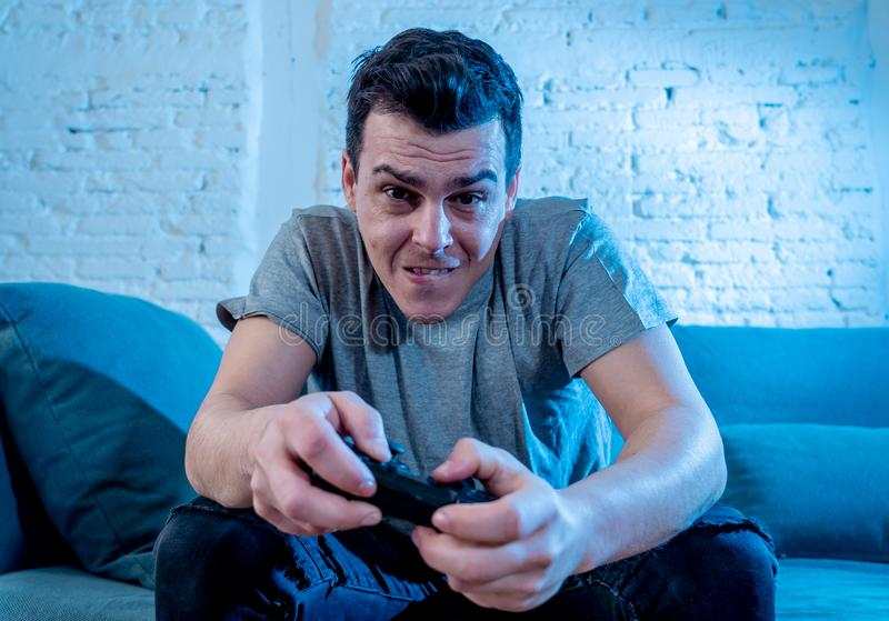Close up portrait of young man playing video game at night addicted to it royalty free stock image