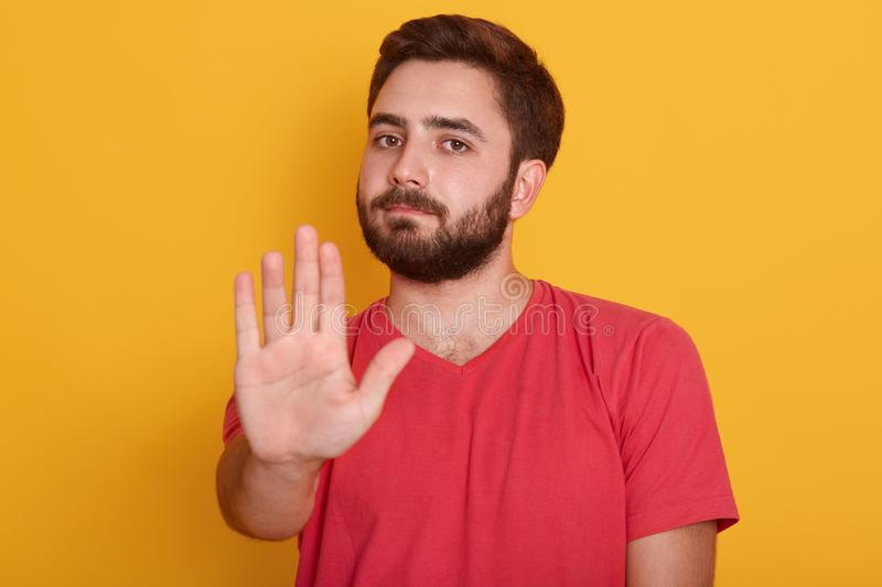 Close up portrait of young man requiring stop with his hand, handsome guy wearing red t shirt, showing stop gesture, isolated over stock photos