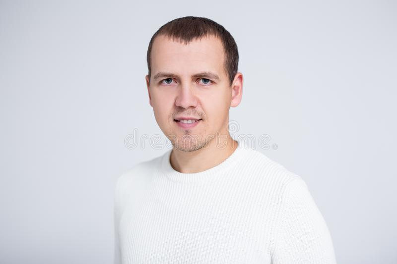 Close up portrait of young man in warm winter sweater posing over gray background stock images