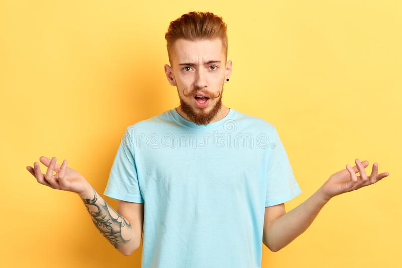 Close up portrait of a young man in white T-shirt shrugging his shoulders royalty free stock images