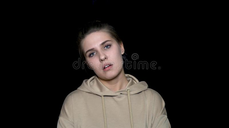Close up portrait of young melancholic female looking at the camera with bored expression on her pretty face, isolated stock image