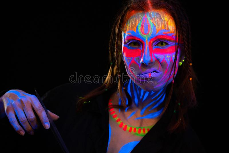 Close-up Portrait of Young naked bold bodyarted woman in blue glowing ultraviolet paint and Yellow eye lenses. Avatar stock photo